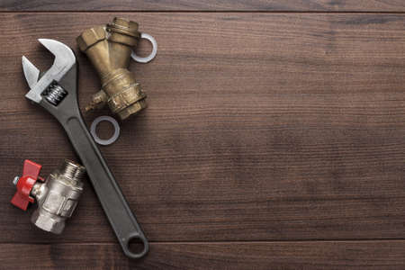 Foto de adjustable wrench and pipes on the wooden background - Imagen libre de derechos