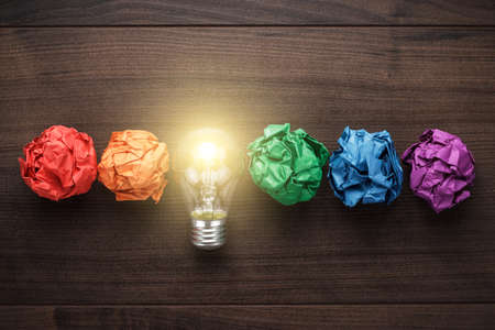 Photo for great idea concept with crumpled colorful paper and light bulb on wooden table - Royalty Free Image