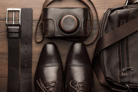 brown shoes, belt, bag and film camera on the wooden table
