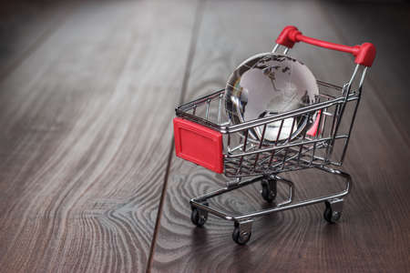 Photo pour glass globe in the shopping trolley global market concept - image libre de droit
