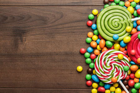 Photo for different colorful sweets and lollipops on the wooden table - Royalty Free Image