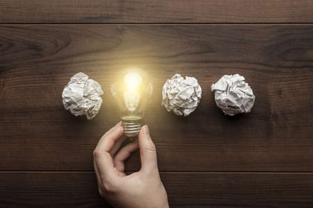 Photo pour new idea concept with crumpled office paper, female hand holding light bulb - image libre de droit