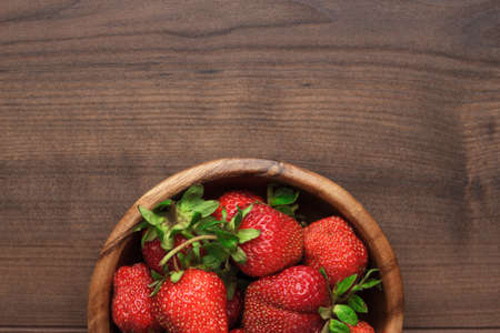 Foto de wooden bowl full of fresh strawberries on the brown table - Imagen libre de derechos