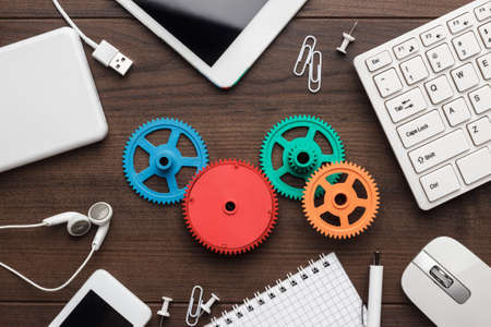 Foto de workflow and teamwork concepts with colorful gears different gadgets and office stationery on the wooden table - Imagen libre de derechos