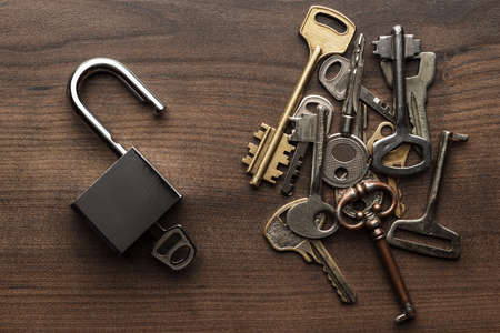 Foto de opened check-lock and different keys on wooden background concept - Imagen libre de derechos