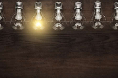 Photo for glowing bulb uniqueness concept with copy space on brown wooden table - Royalty Free Image