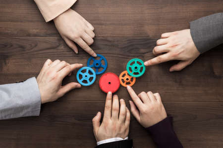 Photo pour Teamwork concept. Different hands of men and women connect colorful gears into working mechanism on the brown wooden table background. Each has its own role in problem-solving. Experience exchange - image libre de droit