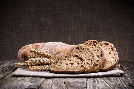 Foto de Slices of bread with rye on a wooden background. - Imagen libre de derechos
