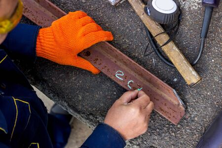 Foto de The worker uses blue chalk to mark, and writes on metal. The line where the worker will cut off a piece of metal corner. - Imagen libre de derechos