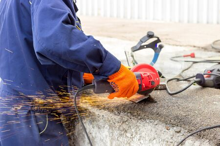 Foto de The worker uses an angle drive grinder to work with a metal corner. Angle drive grinder in action. - Imagen libre de derechos