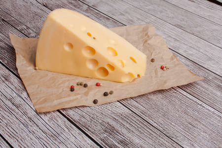 Photo pour Cheese with walnuts pepper on a cutting wooden board on the background. Copy space studio photo - image libre de droit