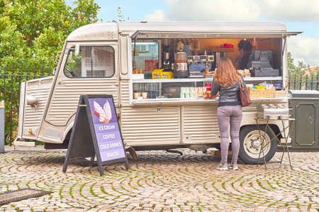 Photo pour Greenwich, London, UK - October 30 2016: Mobile drink and snack and refreshments van on cobbled stones with an unidentified female customer - image libre de droit