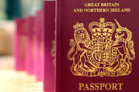 Foto de Five British United Kingdom European Union Biometric passports queueing in a line in shallow focus - Imagen libre de derechos