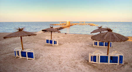 Foto de Natural straw sunshades on a deserted beach with large jetty going into the sea, bathed in warm evening sunshine - space for text - Imagen libre de derechos