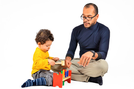 Foto de Father and son are playing together as part of the didactic autism children therapy - Imagen libre de derechos