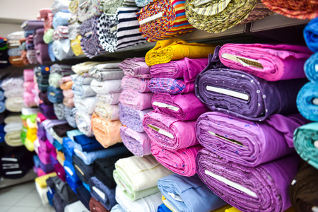 Photo pour Rolls of fabric and textiles in a factory shop. Multi different colors and patterns on the market. - image libre de droit