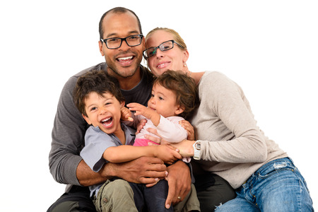 Foto de Happy interracial family is celebrating, laughing and having fun with Hispanic African American Father, Caucasian mother and Mulatto children son and daughter.  Isolated on white. - Imagen libre de derechos