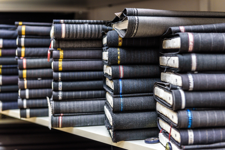 Photo pour Rolls of fabric and textiles in a factory shop or  store or bazar. Multi different fabric for men formal business suit on the market. Industrial fabrics. - image libre de droit