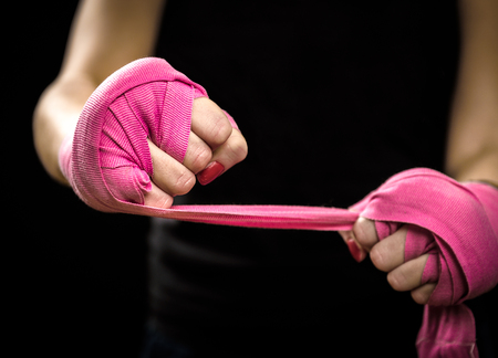 Foto de Woman is wrapping hands with pink boxing wraps. Isolated on black with red nails. Strong hand and fist, ready for fight and active exercise - Imagen libre de derechos