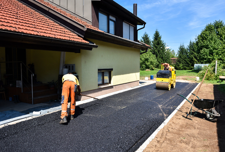Photo for Team of Workers making and constructing asphalt road construction with steamroller. The top layer of asphalt road on a private residence house driveway - Royalty Free Image