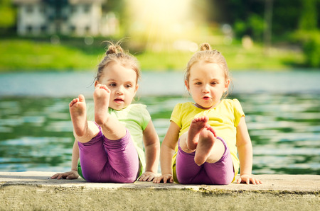 Photo for Twing girls are exercising on a lake shore - Royalty Free Image