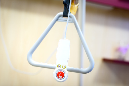 Foto de Hospital bed triangle handle with emergency remote control beacon. Accessories in retirement home helps elderly or ill people get up from bed or call the nurse or a docto - Imagen libre de derechos