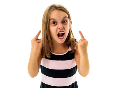 Photo for Little young girl is angry, mad, disobedient with bad behaviour. Children making the act of insubordination and disobedience, yelling, flipping off, showing the middle finger. Act of giving the finger. - Royalty Free Image