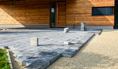 Photo pour Laying gray concrete paving slabs in house courtyard driveway patio. Professional workers bricklayers are installing new tiles or slabs for driveway, sidewalk or patio on leveled  foundation base made of sand at public or private residence. - image libre de droit