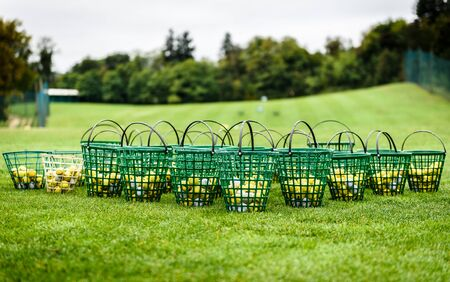 Photo pour Heap of golf balls in basket ready for warm up. Bunch of golf balls in green basket ready on green morning lawn on golf course intended for players warming up with long drive swing. - image libre de droit