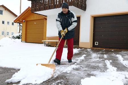 Foto de A man shovels snow in the front of the garages - Imagen libre de derechos