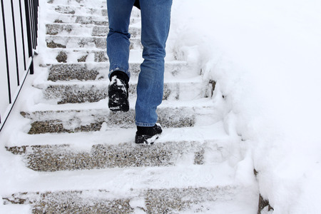 Photo for Risk of slipping when climbing stairs in winter. A man goes up a snow-covered staircase - Royalty Free Image
