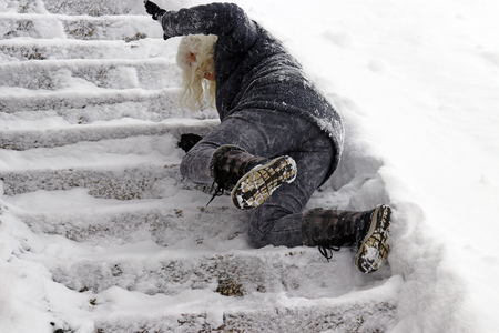 Foto de A woman slips and fell on a wintry staircase. Fall on smooth steps - Imagen libre de derechos