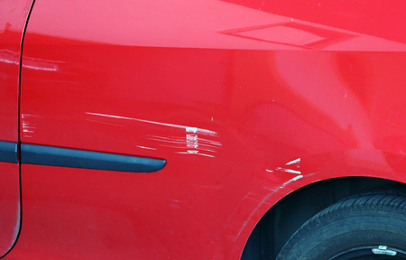 Photo for Paint scratches on a red car. Accidental damage to a red car - Royalty Free Image