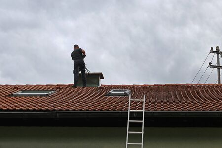 Photo for A chimney sweeper on the roof cleans a chimney with a brush. - Royalty Free Image
