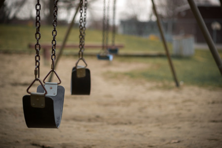 Photo for Children's swings hang empty an idle at a playground on a dull, overcast day. - Royalty Free Image