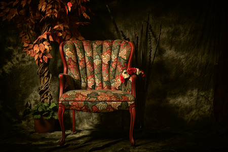 Photo pour An empty, antique patterned chair shot in a chiaroscuro lighting style sitting next to artificial plant. - image libre de droit