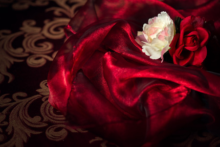 Photo pour A white and red silk rose and carnation sits atop a wadding of luxurious, flowing silk material. - image libre de droit