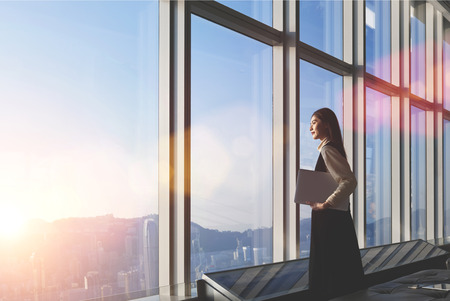 Foto de Successful female office worker with net-book is standing in skyscraper interior against big window with city view on background. Proud asian woman architect looking satisfied with completed project - Imagen libre de derechos