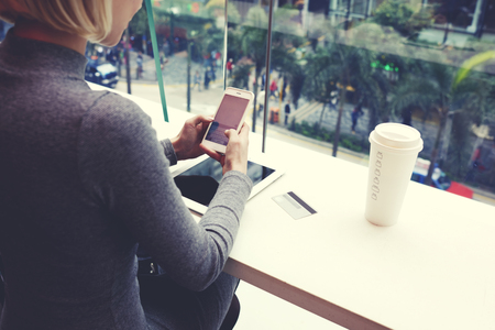 Foto de Closely of woman is typing text message on cell telephone, while is resting in coffe shop of modern shopping center in Hong Kong. Young hipster girl is chatting in social network via mobile phone - Imagen libre de derechos