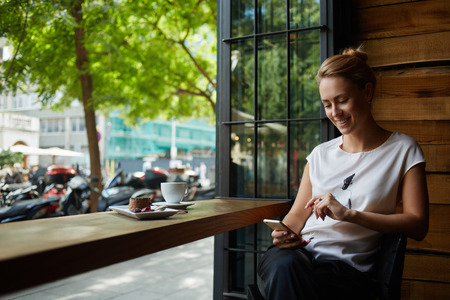 Foto de Charming woman with beautiful smile reading good news on mobile phone during rest in coffee shop, happy Caucasian female watching her photo on cell telephone while relaxing in cafe during free time - Imagen libre de derechos