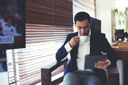 Photo pour Portrait of young elegant men reading e-book on his digital tablet while drinking beverage in cafe inside, confident businessman using touch pad for remote work while enjoying rest during coffee break - image libre de droit