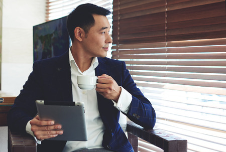 Photo for Portrait of young confident businessman enjoying coffee while work on his digital tablet in office space interior, thoughtful asian man in elegant suit holding touch pad while relaxing in modern cafe - Royalty Free Image