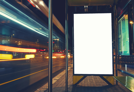 Foto de Illuminated blank billboard with copy space for your text message or content, advertising mock up banner of bus station, public information board with blurred vehicles in high speed in night city - Imagen libre de derechos