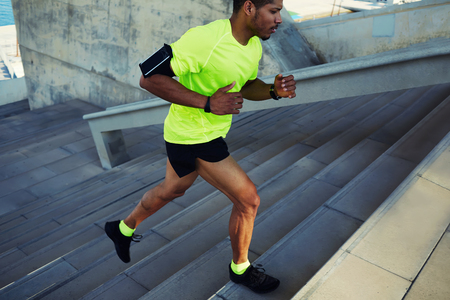 Photo for Cropped shot male dark-skinned athlete running up a flight of stairs with speed, sporty young man in fluorescent t-shirt training or working out outdoors while jogging up the steps, filtered image - Royalty Free Image