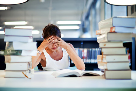 Foto de Frustrated female student sitting at the desk with a huge pile of study books in university library, young asian college student at hard exam preparation in study hall looking tired and weary - Imagen libre de derechos