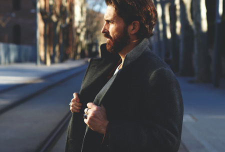 Photo pour Portrait of fashionable well dressed man with beard posing outdoors looking away, confident and focused mature man in coat standing outside at sunny evening, elegant fashion model - image libre de droit