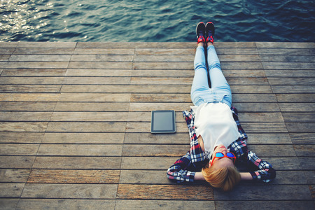 Foto de Top view young woman lying on a wooden jetty enjoying the sunshine,tourist girl in bright glasses lying on jetty by river, vintage photo of relaxing young woman in nature with tablet, cross process - Imagen libre de derechos