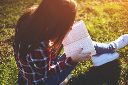 Photo for Pretty relaxed young woman reading a book at the lawn with sun shining - Royalty Free Image