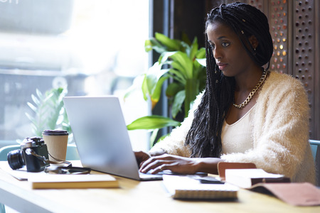 Photo pour Concentrated afro american  freelancer with cornrows typing on keyboard of modern laptop text information in internet websites for searching ideas and - image libre de droit