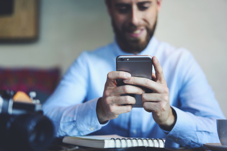 Foto de Young smiling bearded male photographer playing online games using modern smartphone connected to 5G wireless internet completing levels - Imagen libre de derechos